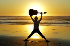 Guitar player on the beach Royalty Free Stock Images
