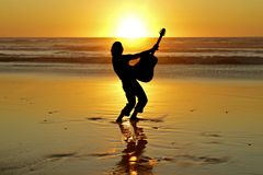 Guitar player on the beach Royalty Free Stock Image