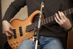 Guitar player body near microphone Royalty Free Stock Photography