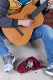 Guitar player collecting money Royalty Free Stock Images