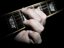 Guitar Player Fingering Chords On Fretboard. Guitar player with fingers on the fretboard fingering a chord with a black background. The guitar neck fretboard has royalty free stock photo