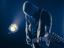 Guitar player in front of spotlight blue tone Stock Photos