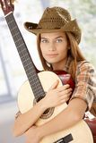 Guitar player girl hugging guitar smiling Royalty Free Stock Images