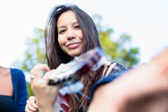 Guitar player girl making music with friends in park Stock Photo