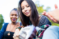 Guitar player girl making music with friends in park Royalty Free Stock Images