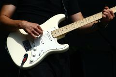 Guitar player hands with electric stratocaster type guitar Royalty Free Stock Photography
