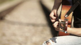 Guitar player hands and instrument neck with railway background stock footage