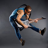 Guitar player jumps. Awesome guitar player jumps with passion in studio Royalty Free Stock Photo