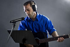 Guitar Player. Male singer holding a guitar and wearing headphones on concrete background Stock Images