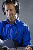 Guitar Player. Male singer holding a guitar and wearing headphones on concrete background Stock Photography