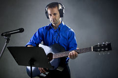Guitar Player. Male singer holding a guitar and wearing headphones on concrete background Stock Image