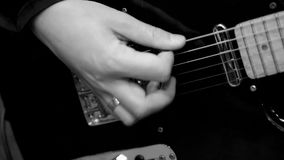 Guitar player. Musician playing electric guitar. Right hand striking the strings. Black and white. Close up. Slow motion stock video