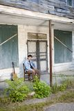 Guitar player on old porch Stock Photo