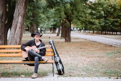 Guitar player in the part. Guitar player siting in the park with classic guitar stock photo