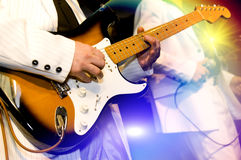 Guitar-player plays an electroguitar. The guitar-player plays an electroguitar, the second person with a microphone on a background, bright multi-coloured light Royalty Free Stock Image