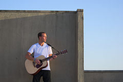 Guitar player on roof playing acoustic guitar Royalty Free Stock Photography