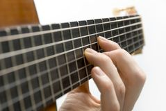 Guitar player's left hand. Classical guitar's fingerboard with playing hand and white background stock photos