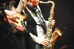 Guitar player and saxophonist on a stage. Musical background, guitar player and saxophonist on a stage with colorful illumination, photo with selective focus and royalty free stock photos