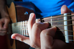 Guitar player. Singer hands on the acoustics guitar playing a song Stock Photography