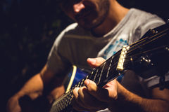 Guitar Player. Singing in a park sitting on a tree Royalty Free Stock Photography