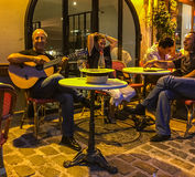 Guitar player smiles at the camera while couple enjoys the moment at outdoor cafe in Paris Stock Photos