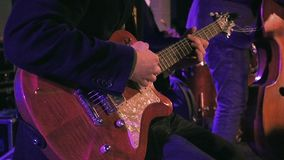Guitar player on the stage slow motion. Guitar player plays the electric guitar on the stage. Jazz or rock concert performance entertainment. Slow motion shot stock video footage