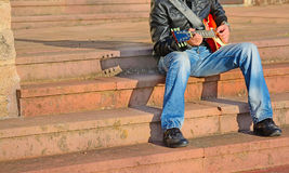 Guitar player on stairs Royalty Free Stock Photography