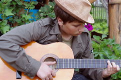 Guitar player teenager with hat outdoors garden  Royalty Free Stock Images