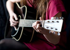 Guitar Player. A woman in a pink dress plays guitar in front of a black background Royalty Free Stock Photos