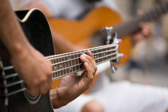 Guitar players. Street guitarists. Musicians are playing on guitars. Close-up of fingers pressing the strings of the instrument Royalty Free Stock Images