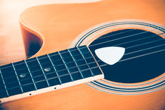 Guitar and plectrum Stock Images