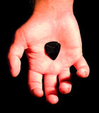 Guitar plectrum in hand Royalty Free Stock Image