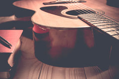 Guitar with Red Book and pen on a wooden table, Vintage style Stock Image
