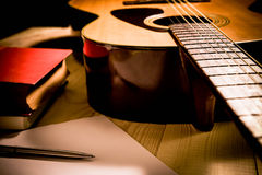 Guitar with Red Book and pen on a wooden table, Vintage style. Royalty Free Stock Images