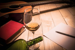 Guitar with Red Book and Wine on a wooden table. royalty free stock photos