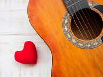 The guitar and red heart on white wooden texture background. Lov royalty free stock images