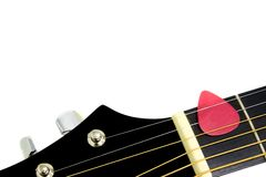 Guitar with Red Pick. Red guitar pick between strings pointing to open white space royalty free stock image