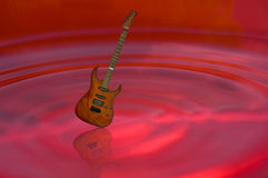 Guitar on red water Stock Images