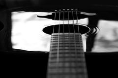 Guitar Reflection. An acoustic guitar reflects back light in a dark environment Stock Photo