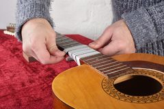 Guitar repair and service - Worker preparation pasting of frets. Musical instrument guitar repair and service - Worker preparation pasting of frets for grinding Stock Image