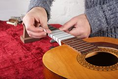 Guitar repair and service - Worker preparation pasting of frets. Musical instrument guitar repair and service - Worker preparation pasting of frets for grinding Royalty Free Stock Images