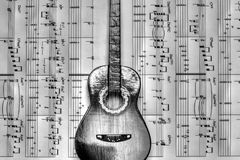 A guitar resting on musical notes