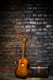Guitar and retro bag on brick wall background Royalty Free Stock Photos