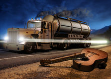 Guitar on the road. Night scene with a broken classic guitar, close to a road on wich is passing a big tank truck Royalty Free Stock Photos
