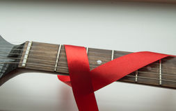 Guitar, rock music and red ribbon - symbol of fight against AIDS.  Royalty Free Stock Photos