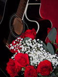 Guitar with Roses. Black Guitar with a bouquet of red roses Royalty Free Stock Images