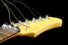 Guitar's head. View at electric guitar neck on a black background Royalty Free Stock Photos