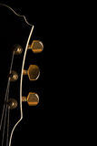 Guitar`s headstock. Black guitar`s headstock on left side of image with gold tuning posts on black background Royalty Free Stock Photography