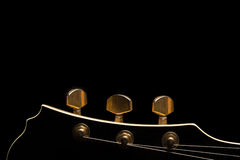 Guitar`s headstock. Black guitar`s headstock on ottom of image with gold tuning posts on black background Stock Photos