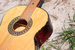 Guitar in the sandy beach. Guitar laying on the ground in the sand Royalty Free Stock Images